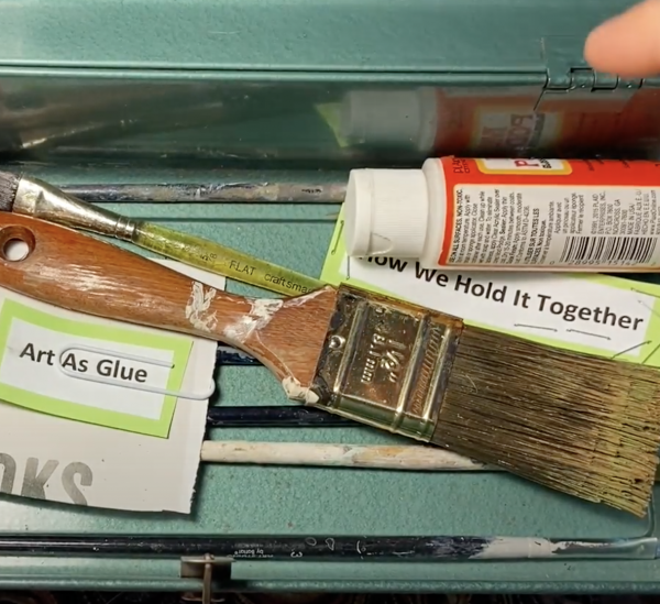 """Green paint box open with a hand reaching in there are various paintbrushes and scraps of paper, one says """"art is glue"""" and another scrap says """"hold it together"""""""