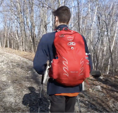 man outside in the woods wearing a red backpack and walking away from the camera
