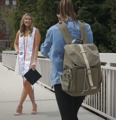 picture of a girl taking a picture of a girl standing in a white dress holding a graduation cap and wearing a graduation stole, they are on a raised walkway