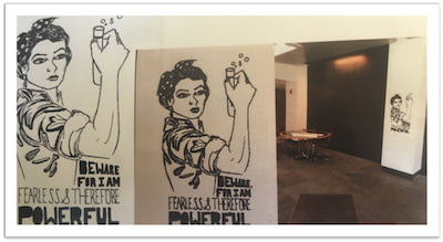 Hand drawn picture of woman holding test tube, drawn on paper, then picture of it placed on wall